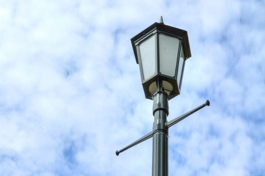 Lamp post against cloudy sky