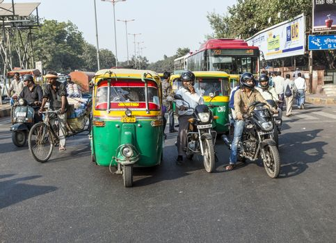 DELHI, INDIA - NOV 11, 2011: Transporting people through city on auto rickshaw in Delhi, India. The classical auto rickshaw is the unique vehicle of local transportation in several Asian countries.
