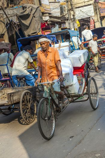 DELHI, INDIA - NOVEMBER 11, 2011: Cycle rickshaws with cargo load in the streets in Delhi, India. Cycle rickshaws were introduced in the 1940's and have a fixed quota of licenses.