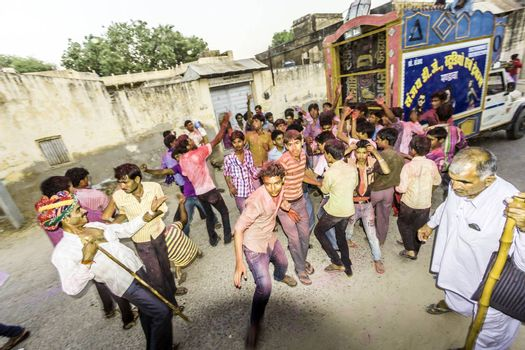 MANDAWA, INDIA - OCT 24, 2012: People throw colors, mostly red, to each other during the Holi celebration in Mandawa, India. Holi is the most celebrated religious color festival in India.
