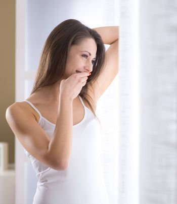 A young woman laughing near window early in the morning