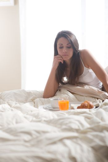 Young woman sitting on bed observing her breakfast