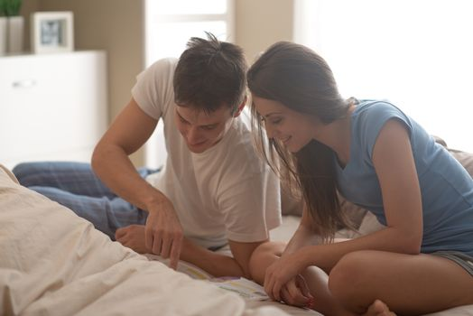 Young happy couple in bedroom reading a magazine