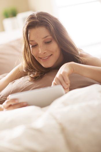 Beautiful young woman using digital tablet in bed