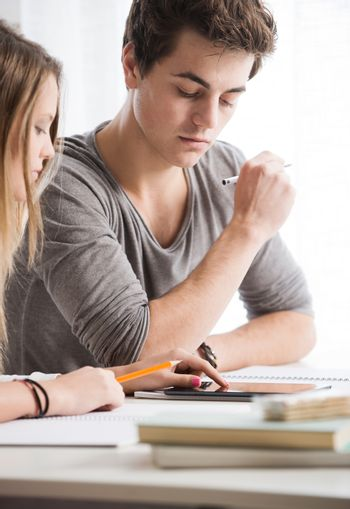 Teen boy and girl sitting together and studying
