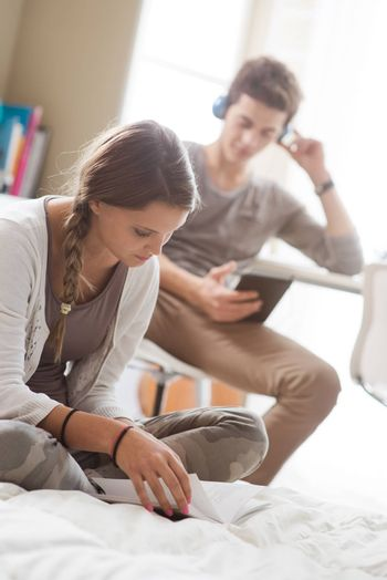 Teen boy and girl at home, sitting and studying. Girl in the foreground.