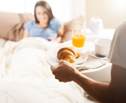 Hand holding breakfast tray to a happy relaxed woman in bed
