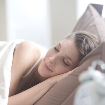 Young beautiful woman sleeping comfortably on bed