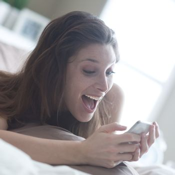 Happy woman at home reading a text message in her bright bedroom