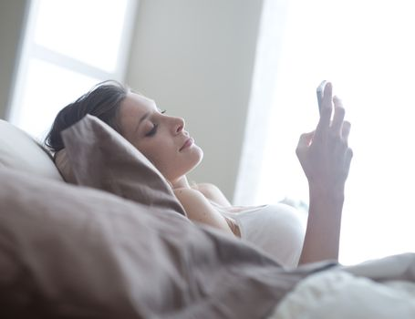 Relaxed woman at home reading a text message in her bright bedroom