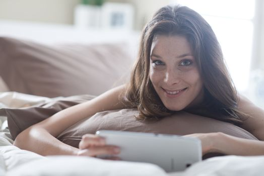 An attractive young female lying on her bed using a tablet