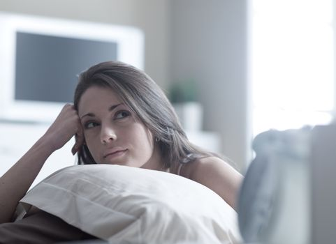 A gorgeous young woman while lying in bed
