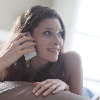 Beautiful young woman talking on the phone while in bed