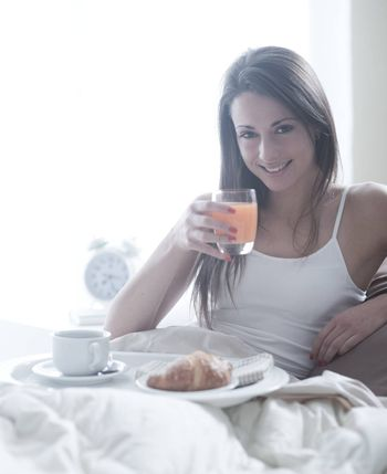 Lovely young woman lying with a glass of orange juice and a tray of breakfast