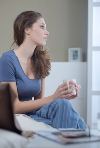 Young woman holding a cup of coffee in bed