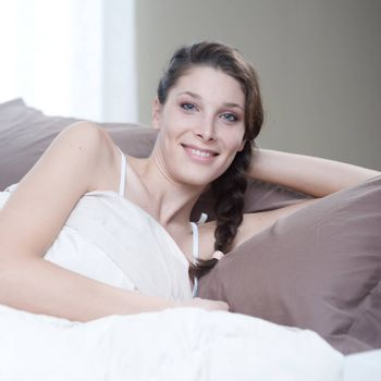 Young woman smiling while lying in bed
