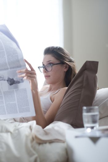 Young woman lying on the bed at home and reading the newspaper