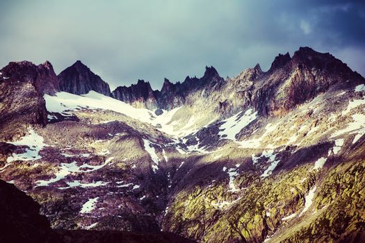 Majestic mountainous landscape, beautiful high Alps in summer covering with snow, grunge style photo, beauty of nature concept