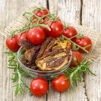 fresh and dried tomatoes on wooden background