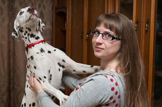 The dalmatian stands on hinder legs leaning on shoulders of the girl