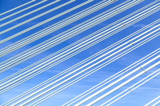 pattern of steel wires of a bridge under blue sky