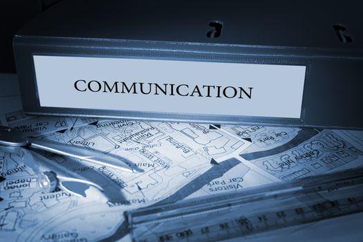 The word communication on blue business binder on a desk