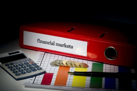 The word financial markets on red business binder on a desk