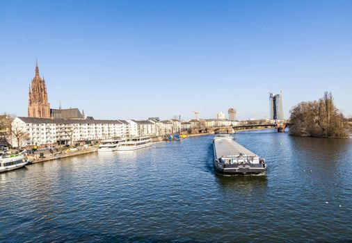 FRANKFURT, GERMANY - MARCH 3, 2013: view to river main with boat and skyline in Frankfurt, Germany. Main river with a length of 527 km is the most significant right tributary of the Rhine.