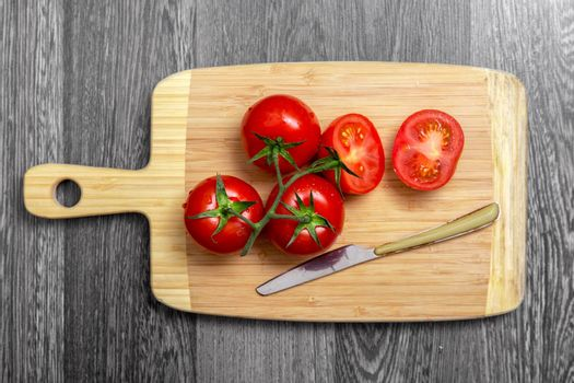 Top view of fresh tomatoes and knife on chopping board on gray table