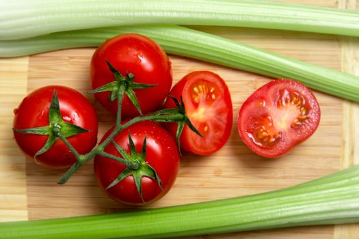 High angle view of bunch of fresh tomatoes and celery sticks on wooden chopping board