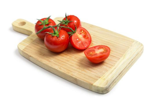 Fresh tomatoes on wooden chopping board, isolated on white background with shadow