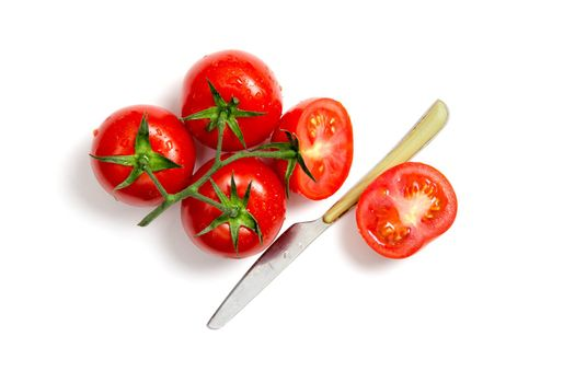 Top view of bunch of fresh tomatoes and knife isolated on white background