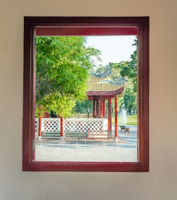 view out of a window to the park in the Sommerpalace Bang Pa In of the King of Thailand near Ajuttaya