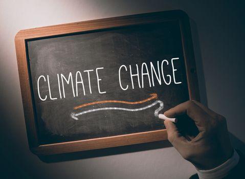 Hand writing Climate change on chalkboard