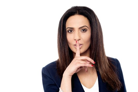 Businesswoman making silence gesture