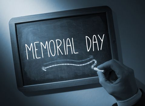 Hand writing Memorial day on chalkboard