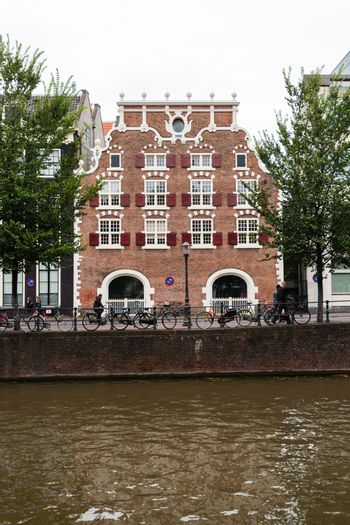 House facade in central Amsterdam beautifully decorated and canal in forefront
