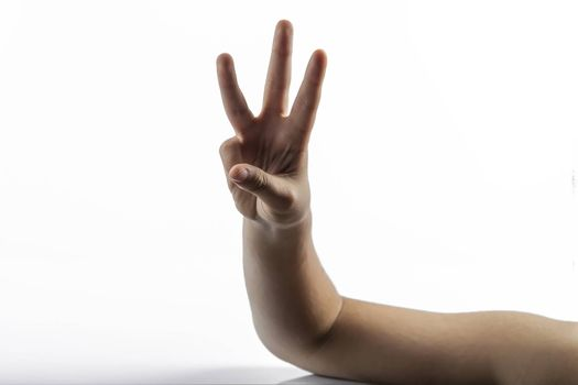 Young hands makes a gesture: number three sign with 3 fingers