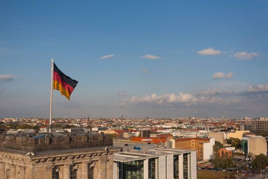 Cityscape of Berlin with German flag in the forefront