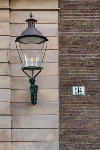 Beautiful street lamp on the wall entrance of a house in Amsterdam Holland
