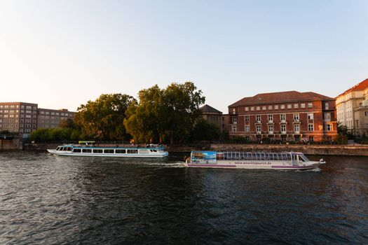Two touristic boats passing each other on the Spree river in East Berlin, Germany