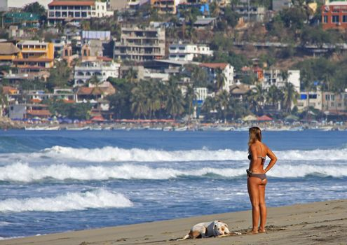 A young lady on a beach with her pet dog in Puerto Escondido, Mexico 25 Mar 2013 No model release Editorial only