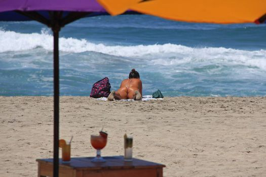 A young lady sun tanning at a beach restaurant in Puerto Escondido, Mexico 26 Mar 2013 No model release Editorial only