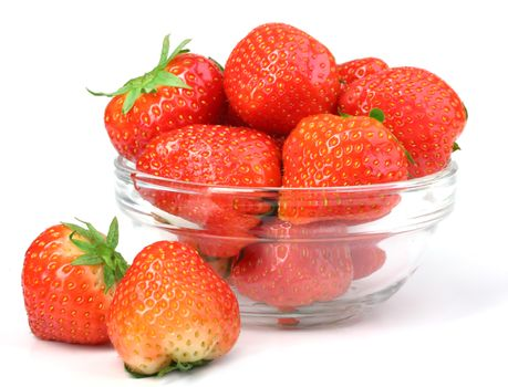 Red strawberries in transparent plate on white