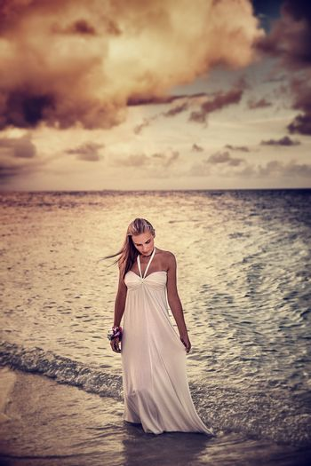 Grunge style photo of beautiful young woman on the beach in overcast weather, dramatic cloudscape, sadness and solitude concept