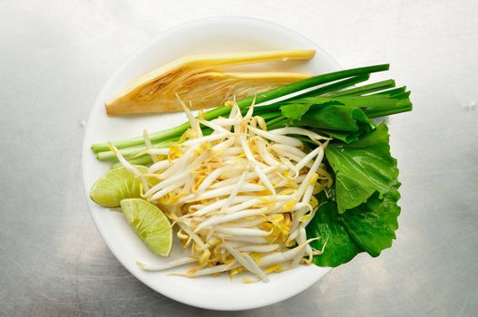 Mix of Thai Vegetable, Bean sprout, lime, banana blossom and Garlic chives on white plate.