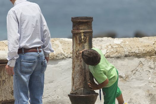 A child drinks water from an old fountain in the old town of Gallipoli (Le) in the southern of Italy