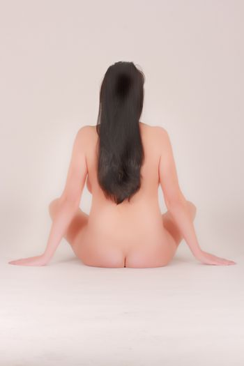 Beautiful naked woman sitting on the floor from behind, with long black hair,