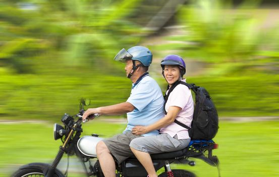 senior couple driving motorcycle with dynamic background