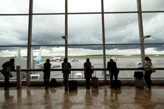passengers on helsinki Vantaa airport waiting and looking out the window at airfield